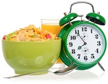 Despertador, cereal y un vaso de jugo
