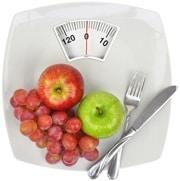 Manzanas, uvas, un tenedor y un cuchillo en la balanza