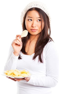 Chica asiática comiendo patatas fritas