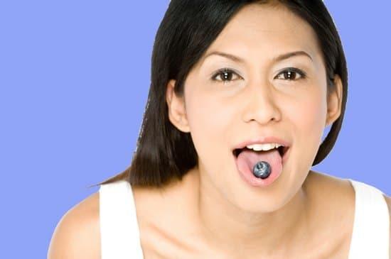 Mujer asiática, con, arándano, en, lengua