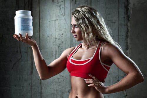 Mujer atlética sosteniendo un recipiente con proteína