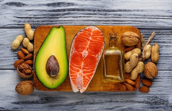 Aguacate, salmón, aceite y nueces en una tabla de cortar de madera