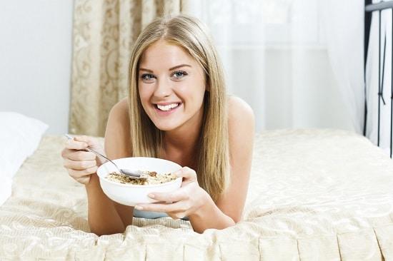 Rubia comiendo avena en la cama