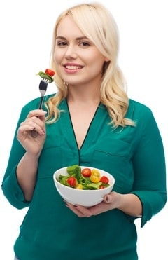 Rubia en camisa verde comiendo ensalada