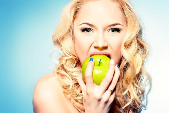 Mujer rubia comiendo una manzana