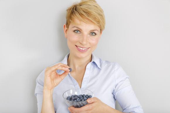 Mujer rubia comiendo arándanos