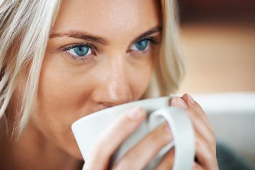 Mujer de ojos azules bebiendo café