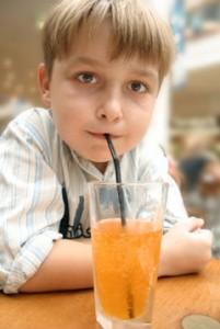 Niño bebiendo refrescos a través de la paja