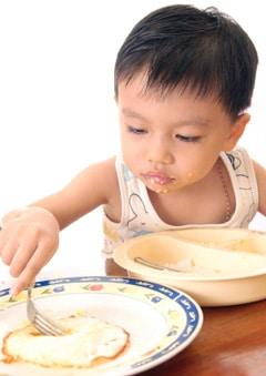 Niño comiendo un huevo frito