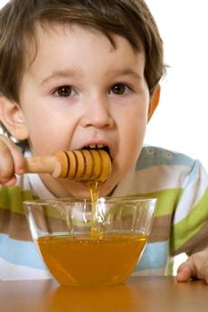 Niño comiendo miel