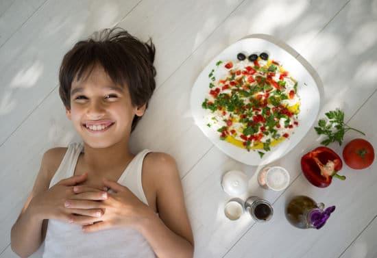 Niño sonriendo con comida mediterránea