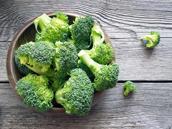 Brócoli en un recipiente sobre una mesa de madera