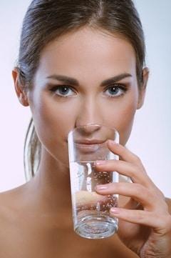 Morena bebiendo de un vaso de agua
