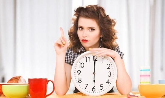 Morena sosteniendo un reloj y esperando para comer