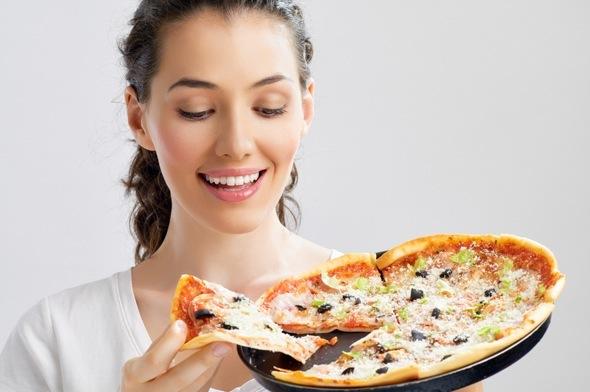 Morena mirando una pizza y sonriendo