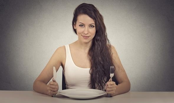 Morena sonriendo con plato vacío y utensilios