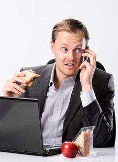 Hombre de negocios, comida, mientras, en el teléfono