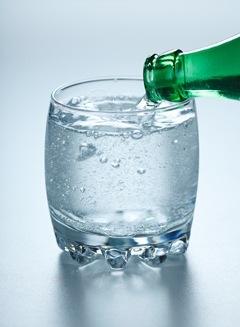 Verter agua carbonatada en un vaso