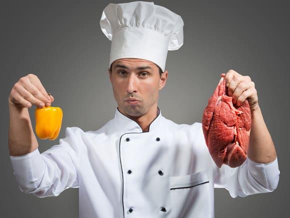 Chef sosteniendo pimiento y carne