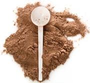 Polvo de proteína de chocolate y una cucharada blanca