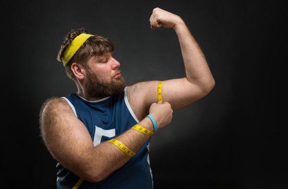 Hombre gordito midiendo el músculo