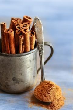 Palitos de canela en una taza y canela en polvo en una cucharadita