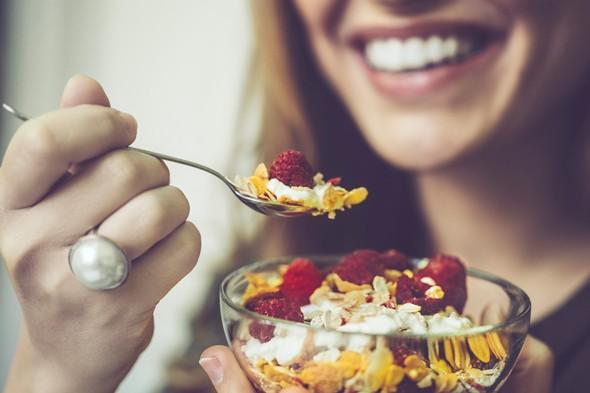 Cerca de una mujer sonriendo y desayunando