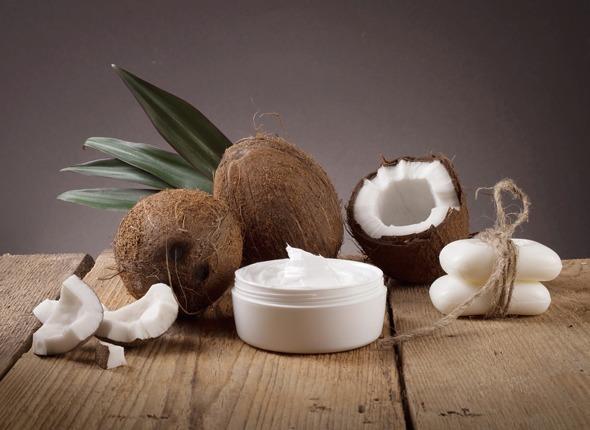 Cocos, jabón y crema en una mesa de madera
