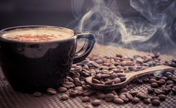 Granos de café y taza humeante