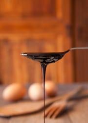 Jarabe oscuro goteando de una cuchara