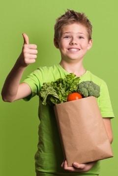 Niño emocionado sosteniendo comestibles