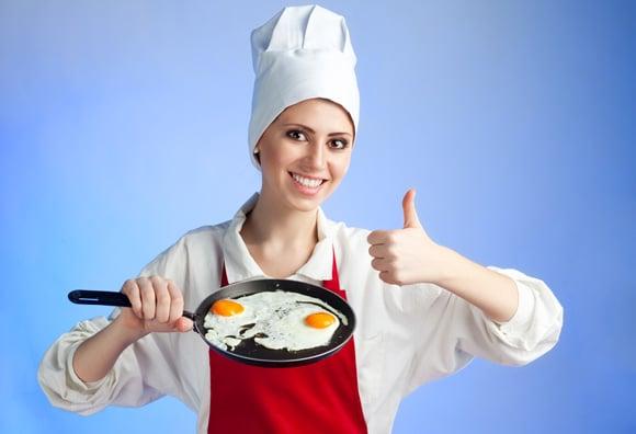 Chef mujer freír huevos