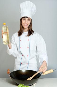 Chef mujer sosteniendo una botella de aceite vegetal