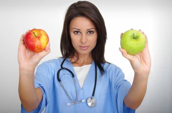 Doctora sosteniendo dos manzanas