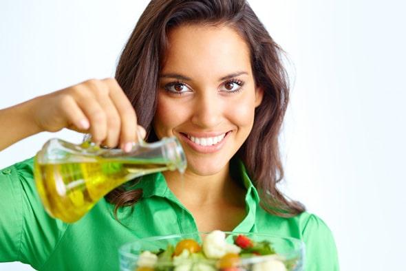 Mujer joven sosteniendo una botella de aceite vegetal