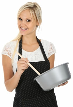 Mujer en delantal con cuenco y cuchara
