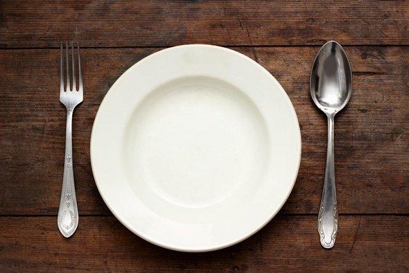 Tenedor, cuchara y un plato vacío sobre una mesa de madera