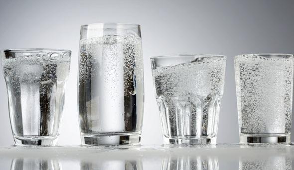 Cuatro vasos de agua con gas carbonatada