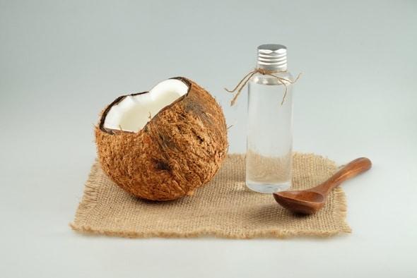 Aceite de coco fraccionado y cuchara de madera y coco