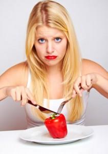 Mujer frustrada comiendo pimiento rojo