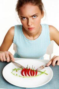 Mujer joven frustrada con verduras en un plato