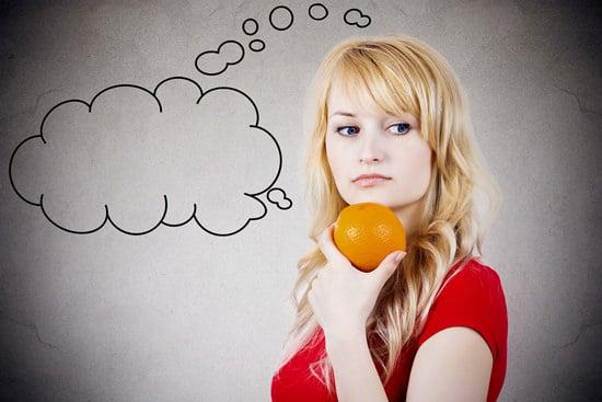 Chica sosteniendo una naranja y pensando
