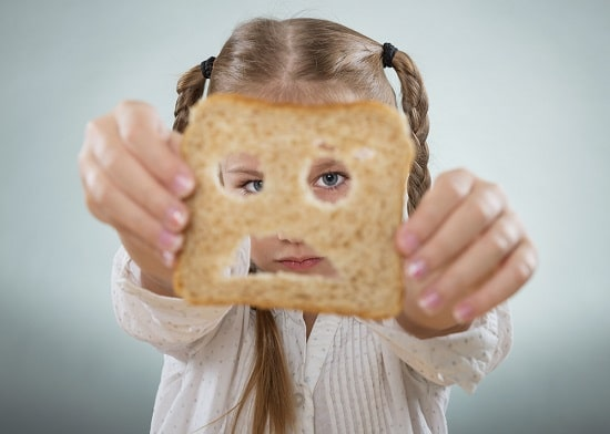 Chica mirando a través de una rebanada de pan