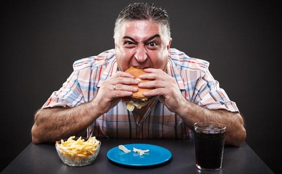 Hombre codicioso y con sobrepeso comiendo comida chatarra