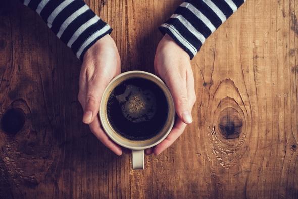 Manos ahuecando una taza de café