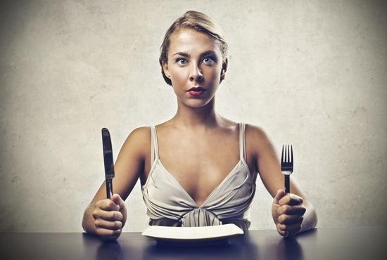 Mujer hambrienta con plato vacío