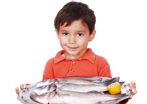 Niño pequeño, tenencia, pez