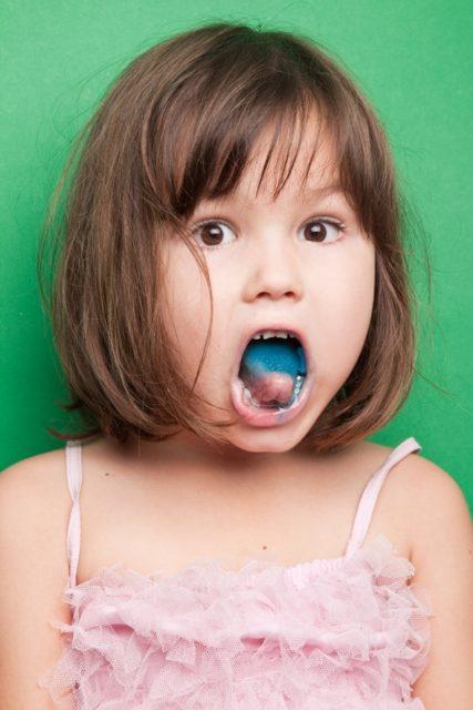 Niña con lengua azul comiendo caramelo azul