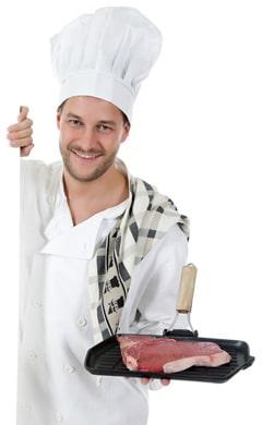 Chef masculino sosteniendo una sartén con bistec