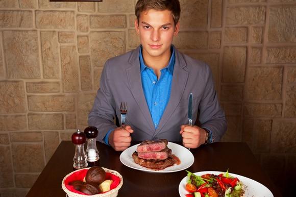 Hombre en un restaurante comiendo bistec